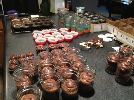 My cupcake workstation displaying Brownie Cupcakes with Chocolate Buttercream and Caramel Sauce and the start of Rainbow Vanilla Cupcakes. You can see my jars, traditional and sample cupcakes all lined up.