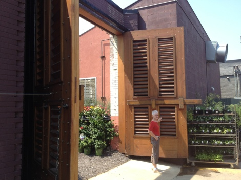 Bowood Farms custom teak doors leading into their urban nursery. Margaret stands by just to show you how huge they really are.