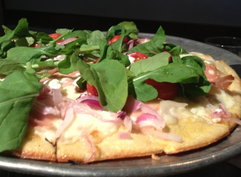 The Central West End pizza from Pi Pizzeria, only found at this location which includes mozzarella, prosciutto, arugula, goat cheese, grape tomatoes and red onions.