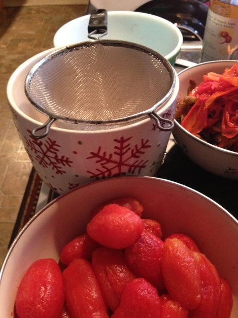 Setup for seeding and chopping tomatoes. Bowl of peeled tomatoes, a bowl where there skins went, a strainer fitted over a bowl to catch the tomato juice, and a bowl for the chopped tomatoes.