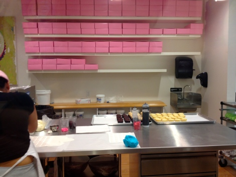 Baking and decorating station at Georgetown Cupcake. The iconic pink boxes in the background waiting to be filled.